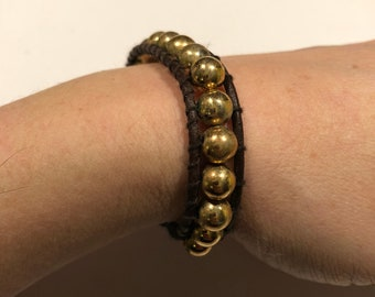 Brown leather ladder-stitch bracelet with gold-tone beads and Chinese coin closure