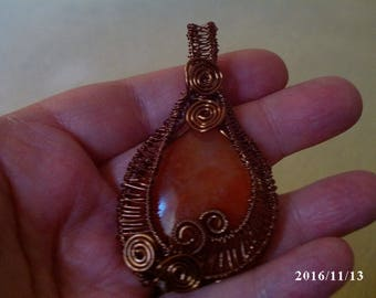 Intricately wire wrapped orange agate stone with antique bronze wire