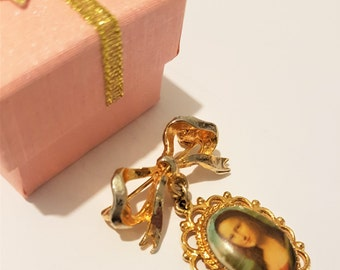 Vintage pendant brooch, shawl pin or scarf pin, with a gold tone tied bow and pendant portrait of the Mona Lisa, 1960s