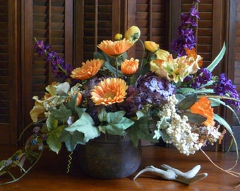 Autumn floral arrangement in orange and amethyst.  Rich fall color contrast in this large arrangement.