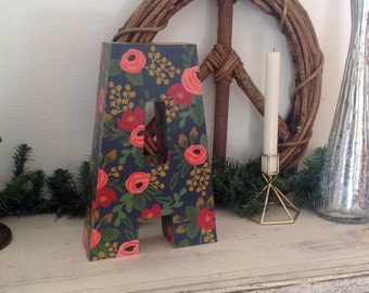 Upcycled capital cardboard wall letter covered in RIFLE PAPER
