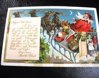 Carte postale Vintage 1906 avec Père Noël et traineau volant à travers la nuit, des jouets sur le dos