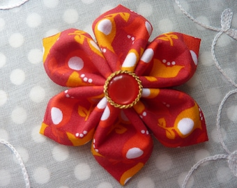 Kanzashi flower brooch in orange with small red and gold button with red fabric