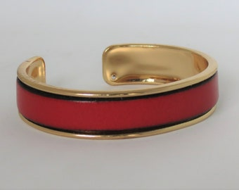 Bangle, metal and red leather.