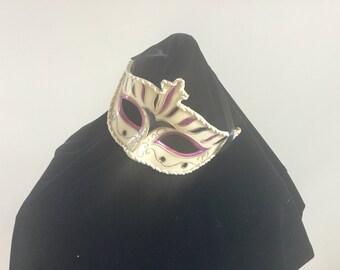 Cream and purple masquerade mask.