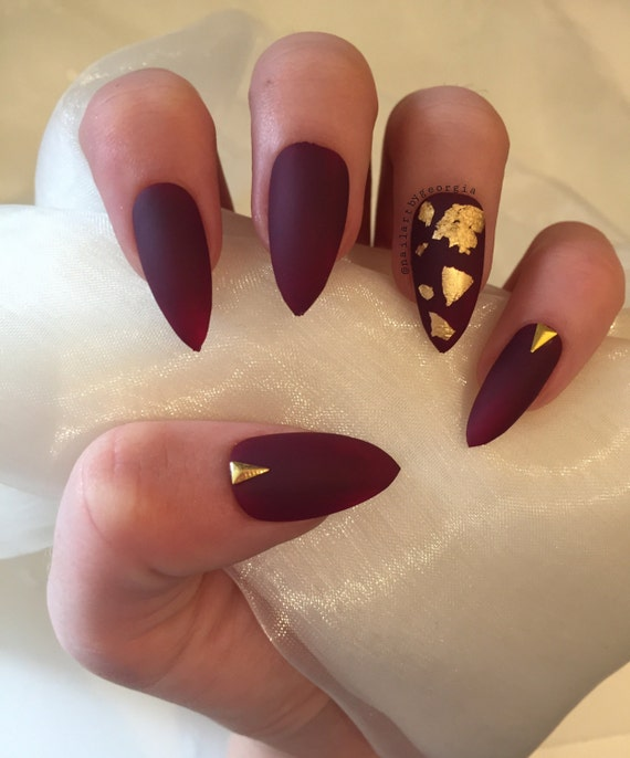 Matte burgundy stiletto false nails with gold leaf and studs