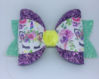 Floral unicorn bow with purple glitter loops,unicorn printed leatherette mint green tails and yellow velvet centre.
