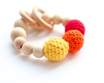 Teething toy with crochet wooden beads and 2 wooden rings. Yellow, red, orange alternately small and big wooden beads rattle.