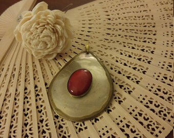 Oval pendant with deep red accent stone