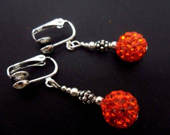 A pair of pretty orange shamballa style dangly clip on dangly earrings.