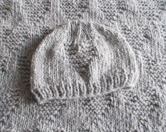 Cover and baby hat in knitted wool with hearts.