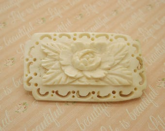 A beautiful hand carved flower and leaf design antique jewelry brooch in deep carved openwork cream coloured celluloid or bovine bone