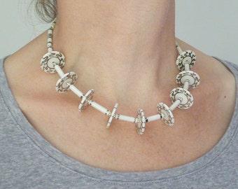 Porcelain discs necklace, transparent glazed porcelain with wiggle design in platinum, fine tubes with platinum lustre, silver clasp