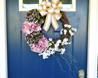 luxurious spring or summer wreath with pink hydrangeas, small white blossoms and burlap bow. Indulge in a handmade, high quality wreath.