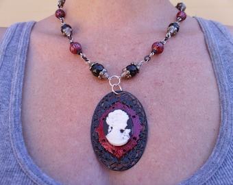 Cameo set in a red frame on top of a black flower filigree beaded necklace