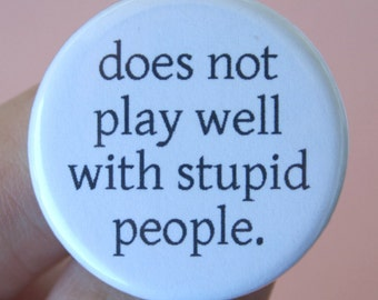 does not play well with stupid people.  1.25 inch pinback button. it's not your fault you are surrounded by idiots.