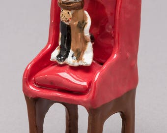 Hand made, ceramic/ clay sculpture of a calico cat sitting on an arm chair.