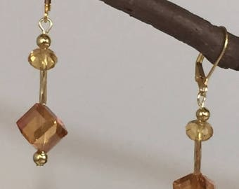 Go for the gold and amber with these amber crystal cube drop earrings.