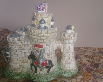 Castle decorative teapot with a knight outside and Norman soldiers peeping over the battlements. The drawbridge forms the spout.