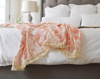 The Throw Blush Ikat Muslin Blanket with Fringe Trim