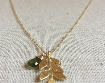 Gold necklace with leaf charm and a green tourmaline gemstone