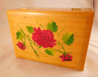 Vintage wooden box with roses painted on the lid.