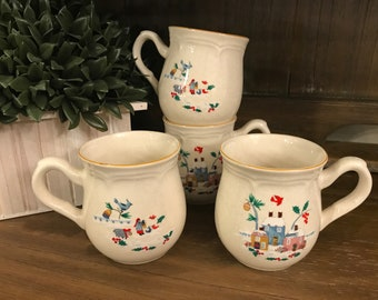 Set of 4 Holiday Mugs In Heartland Christmas by International - Winter Scene - Homes With Snow - Birds - Holly