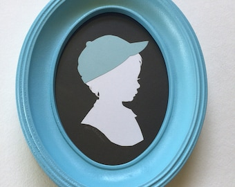 FRAMED Custom Silhouette Portrait: 5x7, White Silhouette, Black Background, with Color Embellishment, in Light Blue Oval Frame.