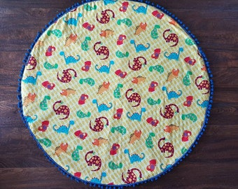 Handmade round padded dinosaur print baby play mat with blue pompom trim /READY TO SHIP