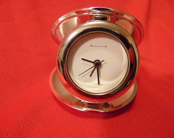 "One (1), 3"" Diameter, Silver Plated, Folding, Quartz Analog, Travel Alarm Clock, from Newbridge."