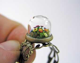 Miniature flower garden in a a glass dome. Adjustable brass ring.