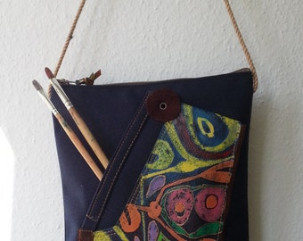 A unique handmade purse/bag with a manual abstract painting .