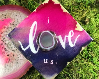 """Purple, pink and gold hand lettered """"i love us"""" on canvas"""