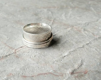 Twirling patterned silver ring with double movement singles