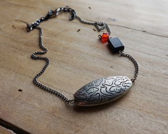 Asymmetrical pendant with red, black and silver accents.
