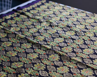 Narrower piece of black fabric with orange, yellow green and gold