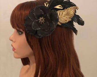 black flower with large gold feather fascinator