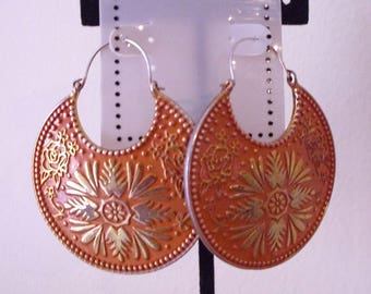 Vintage large round orange earrings with raised design on fronts. Wire.