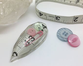 Sewing inspired resin brooch with tape measure, pin and buttons.