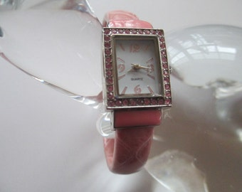 Lady's watch, tiny pink crystals surround face of watch.  Quartz , pink leather moveable cuff'  not signed used watch