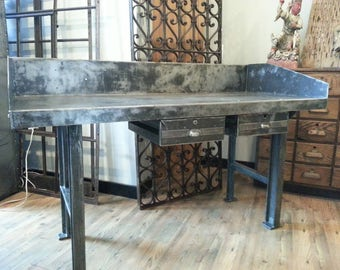 Vintage industrial stripped steel factory table with cast iron legs