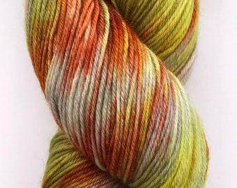A beautiful, soft, hand dyed yarn in shades of grey, orange, yellow and green on a merino, nylon base.