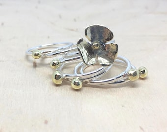 Stackable ring set made out of silver and bronze rings with dots and flowers