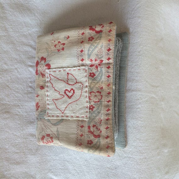 Needlecase in worn, faded vintage linen with red roses, blue ribbons, embroidered with dove & heart