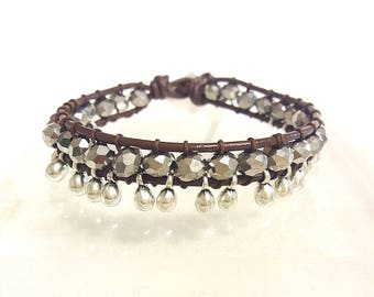 silver charm on brown leather bracelet