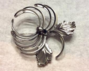 Silver metal floral flower hurricane brooch pin