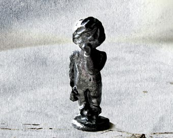 vintage pewter child in pajamas with back flap and thumb in mouth, collectible
