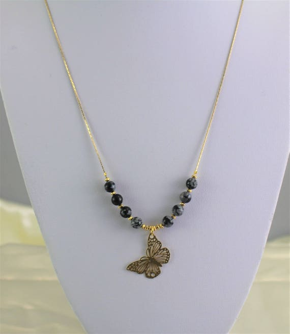 black and white necklace with precious stones and filigree golden butterfly
