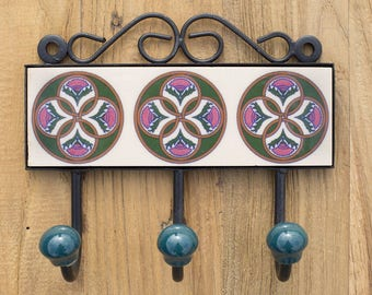 Three metal hooks with ceramic tile.Traditional Indian design.