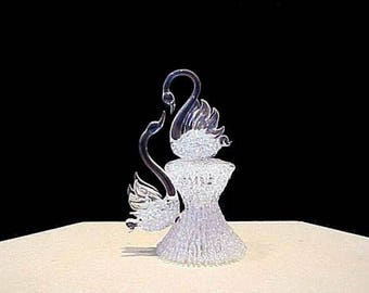 This swan cake topper has two swam reaching for each other on a knitted glass base.